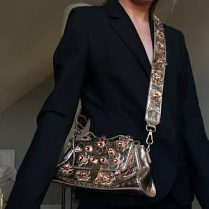 """Handbag i roséguld med blommor och stenar. Dess yta är liksom """"crusty"""" (bild 3), som ger en coolare look! Använd, men fortfarande i rätt bra skick! Fraktkostnad: 55kr spårbar"""