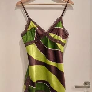 Ett brunt/ grönt linne med spetsdetaljer. Trendiga färger och den där snygga spets criss-cross detaljen. Är längre i modellen med små spetsslitsar längst ner, men har stor potential som en crop top också;)