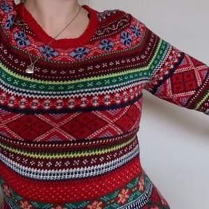 Julig tröja med massa mönster. Röd i grunden.