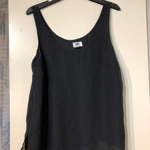 Svart blus/linne i storlek M med flera lager detaljer i ryggen.
