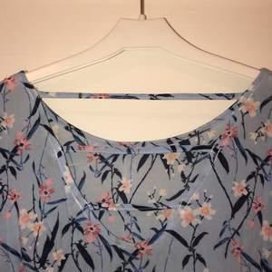 Blommig blus i blå, vit och rosa. Fin rygg som är lite öppen, se bild 1! Kortare vida ärmar! Tunn och luftig och perfekt till sommaren🥰 säljer för 50kr, du står för frakten🥰