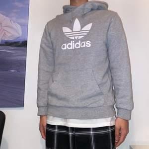 En grå Adidas Orginals Hoodie i storleken SMALL. Det är en vintage stilfixerad hoodie och den sitter som svensk medium då den är amerikansk storlek. Hoodien köptes 2018 i San Fransisco men har ej använt den på över ett år!DM VID INSTRESSE ELLER FRÅGOR <3