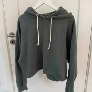 En mörkgrön kort hoodie från bikbok i stl S💞 Säljer pga av att den inte kommit till användning✨ Dessutom har den knyten både vid kragen och nere som man kan spänna åt!!