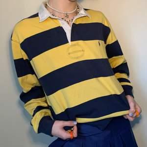 Vintage oversized marinblå och gul randig Ralph Lauren tröja med vit krage och broderad logga på vänster bröst 🧵 Tröjan är så, så, så mysig, storleken är optimal för att både kunna ha den runt hemma men också för en skön vardagsoutfit! Den passar som bäst med ett par mörkblåa byxor och vita sneakers för att komplettera tröjans färger! Notera på sista bilden att tröjan har några små svarta prickar, ett pyttelitet igensatt hål under loggan och en vag blå fläck på ena sidan av kragen!
