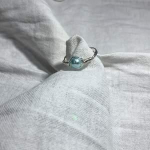 En hemmagjord ring med silverfärgad metal och har en liten blå pärla på. Fin att ha till mycket.