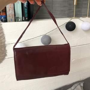 Superfin vinröd vintage handväska. Fint skick och har en söt liten spegel i som faktiskt är väldigt bra!