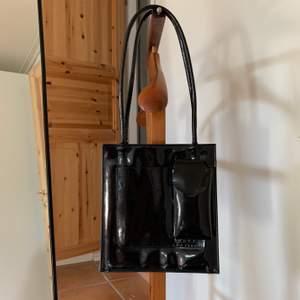 En glansig handväska köpt 2hand. Håller inte för hur tunga föremål som helst. Finns 4 st fickor. Höjden är 23cm och bredd 21cm. 🥰