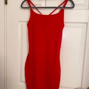 Röd klänning med korsning på ryggen, figursydd, endast använd 1 gång.