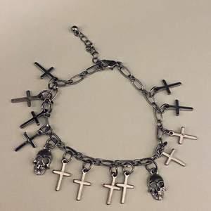 Ett armband. Det finns kors och två skallar på det. Armband är i silver och det är endast använt en gång. Det är i bra skick.