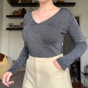 Skön tunt stickad v-ringad tröja i svart med silvertråd. Nyskick. Finns ej att köpa i Sverige.