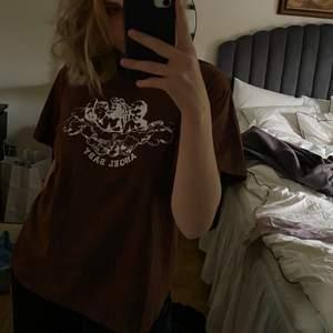 """Säljer denna oversize T-shirt med fett coolt tryck där de står """"ANGEL BABY"""". Brun fin färg, så skön 😍 skulle säga att den passar alla beroende på hur man vill att den ska sitta. Pris kan diskuteras vid snabb affär 💗"""