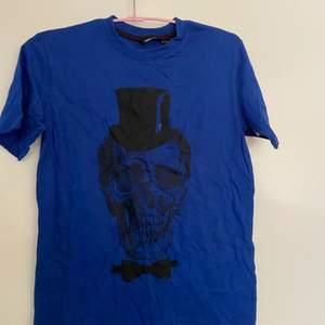 Blå dödskalle T-shirt från Lindex, i strl 146-152 men sitter mer som en S