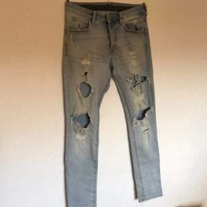 Ljusblå jeans med tre hål på vardera sida + slitningar. Bra skick och väl använda. Har fyra knappar för att stänga. Från H&M.