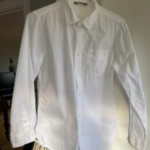 Fint skick då den knappt är använd. En ficka där fram med en liten fågel som detalj. Vita knappar längst ner på armarna och på framsidan av skjortan.