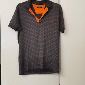 En grå Polo( Ralph Lauren) T-shirt med oranga prickar. Köptes för 2 år men har inte används sedan de första 3 månaderna efter köpet. T-shirten är k storleken L.
