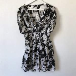 Oanvänd mönstrad klänning från Vila i svart/grå/vit. Resår i midja och korta ärmar, V-ringad, lite krispigt bomullstyg men ändå fint fall.  Kan mötas i Stockholm eller skicka mot fraktkostnad! ✨🌸✨