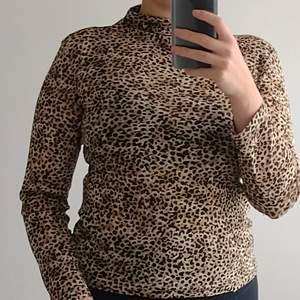 Leopard mönstrad tröja i tunt, genomskinligt tyg och med liten polokrage. Inköpt på Humana. Stretching tyg och kan nog passa dig med storlek S-L (jag har oftast M).