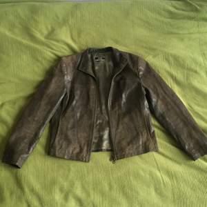 Cool skinnjacka i grönt läder i ormskinnsmönster. Jag säljer den billigare då det finns en fläck bak på ryggen, se sista bilden.