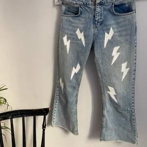 Handmålade jeans originellt från ASOS målade med vita blixtar i en cropped flare modell. Jeansen är i bra skick och kvaliten är hyfsat tjock. Storlek: 26/28.                 Buda nere i kommentarerna! Högsta bud: