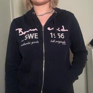 Marinblå zip up hoodie från Bondelid med broderat tryck på bröstet. Aldrig använt, nyskick. Mycket härligt material