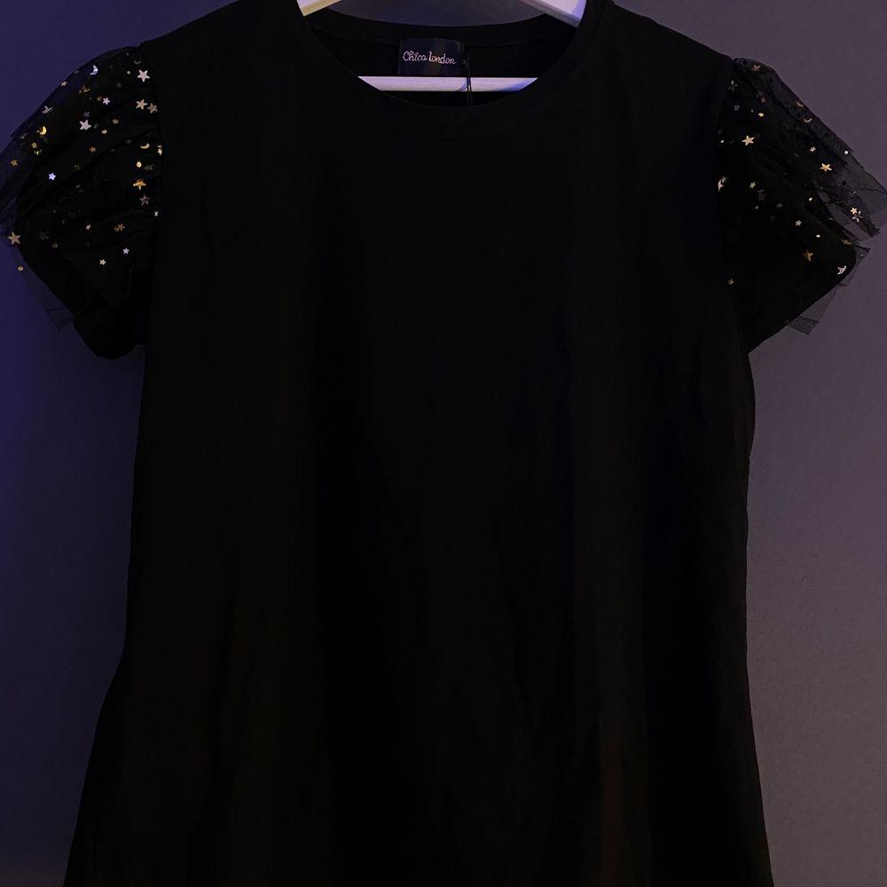 """Festlig t-shirt med stjärnor på 🤩 (skriv för tydligare bild) Helt oanvänd och säljer därför att det inte längre är min """"stil"""". Strl S och säljer för 100kr + frakt 🖤. T-shirts."""