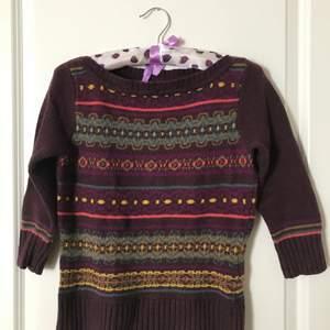 A dark-maroon sweater with an ornament by UK brand Monsoon with an elbow-length sleeves. Warm and soft. 10% wool, 30% cotton, 30% acrylic, 30% nylon. Very good condition. Köparen står för frakten.