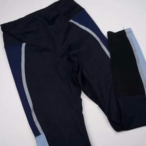 Svarta träningstights med snygga detaljer som ljusblåa/mörkblåa fält och praktisk mest vid slutet av benet. Dessutom silvriga linjer som är i reflex - perfekt  för att sporta ute vid mörker. Se fler trendiga träningskläder på vår Instagram @oak_uf!