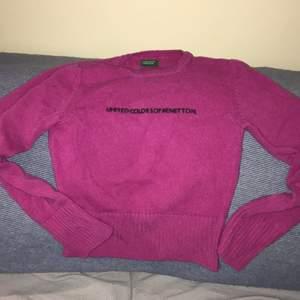 Kall-rosa tröja i ull. Texten är i något slags filtmaterial och sticker ut lite från tröjan.