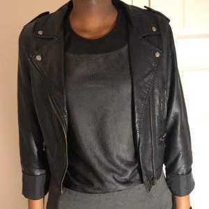Svart skinnjacka i storlek XS. Köpt från JC längesen. Svarta linnet under jackan får du på köpet. Den är ganska genomskinlig men fint med en svart BH under. Jackan är knappt använd.