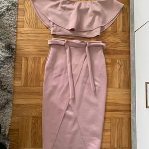Jättefint matchande set med off shoulder top och högmidjad kjol. Färgen är lila/rosa