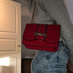 Röd väska från Top shop i fantastiskt skick. Går att ha crossbody eller som axelväska. Bara att fråga om du har några funderingar. Mått: H14 cm x B19 cm.