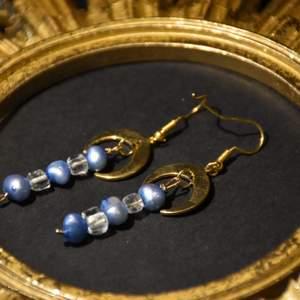 Örhängen med guldiga halvmånar och bergskristall samt blå sötvattenspärlor. Krokarna är nickelfria.