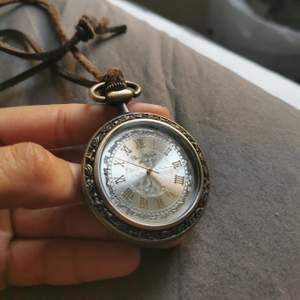 Modern klockurs-smycke med läderband på ca 40 cm. Batteriet till klockan fungerar ej.
