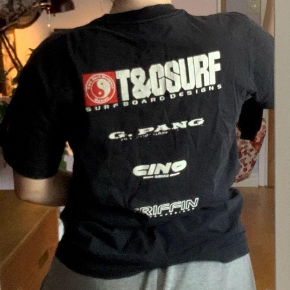 Cool svart T-shirt i storlek L. Den är i bra skick och har en massa tryck på sig om surfing. . T-shirts.