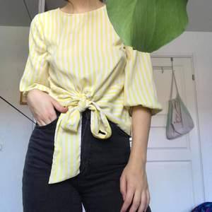 Sommrig citrongul blouse med puffiga armar och knyt i framdsidan.