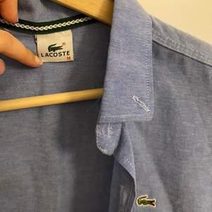 En klassisk blå skjorta från Lacoste. Storlek M men passar S/XS. I bra skick.