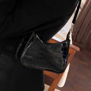 En liten svart väska från med glossig svart färg.               Endast använt 1 gång, säljer då jag har en liknande.        Väskan har inga skador👌🏻                                                   Köparen står för frakt 🚚