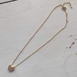 Halsband från guldfynd med ett hjärta på. Välgjort