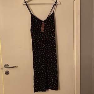 Blommig klänning som går till knäna ungefär. Slits på båda sidor strl. 36 (oanvänd)