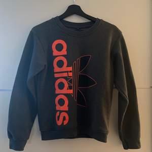En grå Adidas tröja med orange tryck. Storlek S, passar xs och m. Använd fåtal gånger så perfekt skick. 150kr plus frakt eller högsta bud💞