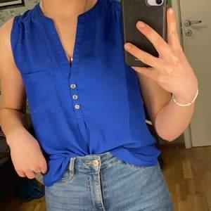 Blå blus med urringning från H&M. Använd men i bra skick.