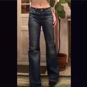 """Blå jeans från Acne i modell """"A-pant Lena"""". Storlek 28/34. Sitter lite löst på mig som vanligtvis är en storlek 28 i jeans och 175cm lång. Köpta secondhand men de är aldrig använda efter det. Köparen står för frakt. Frakt 96 kr."""