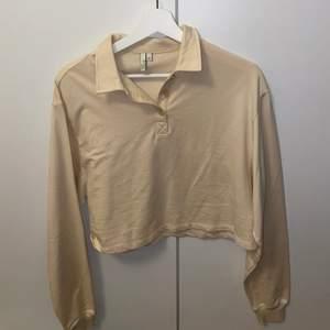 Croppad sweatshirt med krage i beiget från Nelly i storlek XS
