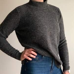 En finstickad tröja med hög krage, i storlek M. Färgen är en blandning på brun och grå.