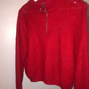 En röd stickad tröja med en drag kedja vid halsen som går att dra ner och upp. Tröjan är andvänd två gånger och har legat i en garderob i två år helt orörd, så den är i ett bra skick.