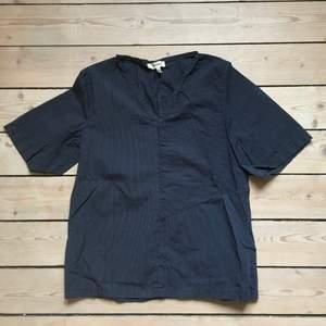 T-shirt i mörkblå med smala vita ränder. Nypris: 1300:-