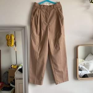 Super snygga kostymbyxor från hm i ljusbrun/beige färg. Aldrig använda och därför i nytt skick, storlek är 34