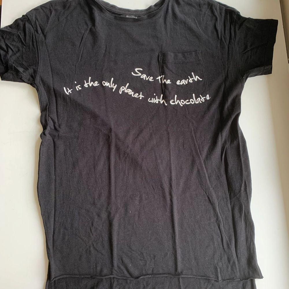 """Svart t-shirt med en liten fick på vänster sida. På det vita trycket står det """"Save the earth It is the only planet with chocolate"""". Längre tyg bak och en liten slits i sidan. Fint skick och super skönt material. Stl XS från Bershka. Tröjan koster 30 kr, frakt ingår ej. Swipe för fler bilder.. T-shirts."""