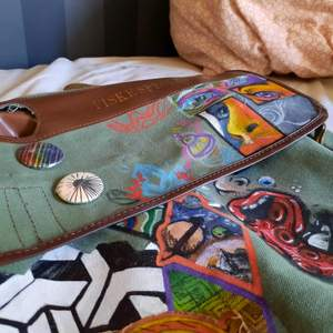 Väskan är gammal (80 tal) och handmålad på framsidan. Två pins sitter på (se bild 3). Bra kvalite utan några större skador  finns tecken på slitage på insidan av väskan (trådar som sticker ut lite). Två ytter fack och ett stort fack inuti väskan.