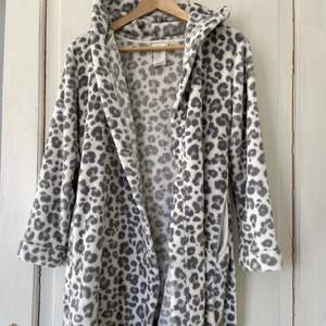En gullig leopardmönstrad morgonrock i vit & ljusgrå, är använd men i fint skick💓 den har två söta små öron på luvan, är i storlek 146/152 och funkar som XS eller S om man inte har för långa armar, finns två fickor på sidorna